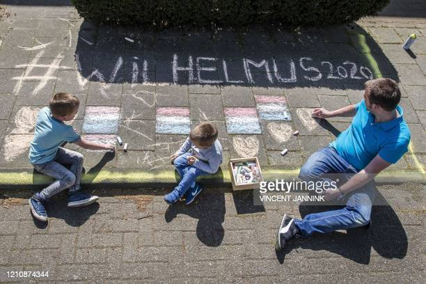 Ronald Kommelt and his children Daan , Teun use chalk to write 'Wilhelmus' on the pavement outside their home in Borne, eastern Netherlands on April...