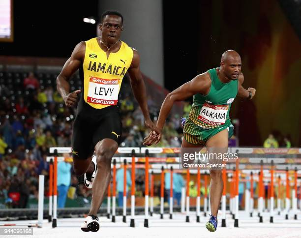 Ronald Levy of Jamaica crosses the line to win gold ahead Antonio Alkana of South Africa in the Men's 110 hurdles final during the Athletics on day...