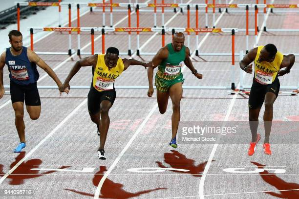 Ronald Levy of Jamaica crosses the line to win gold ahead of Hansle Parchment of Jamaica in the Men's 110 hurdles final during the Athletics on day...