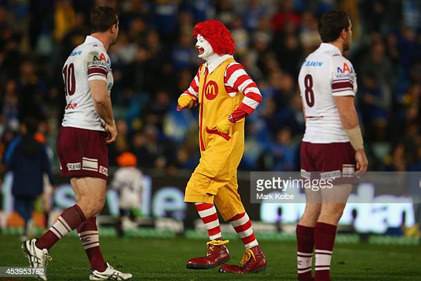 Ronald McDonald runs by Brenton Lawrence and Josh Starling of the Sea Eagles before the start of the round 24 NRL match between the Parramatta Eels...