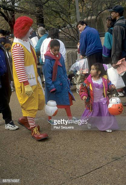 Ronald McDonald walks the grounds of Lincoln Park Zoo entertaining children during a Halloween event Chicago Illinois 1980s Children in costume are...