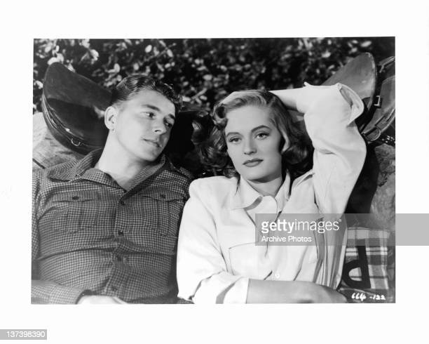 Ronald Reagan lies on the ground next to Alexis Smith in a scene from the film 'Stallion Road' 1947