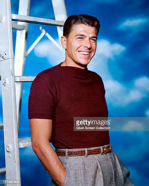 Ronald Reagan US actor wearing a brown tshirt and grey trousers leaning against a metal stepladder smiling in a studio portrait against a background...