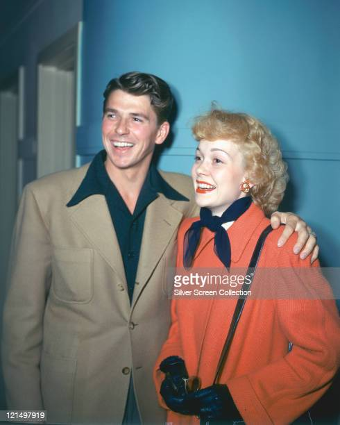 Ronald Reagan wearing a beige jacket with dark blue shirt with a wide collar and his wife Jane Wyman US actress wearing a red coat with a dark blue...