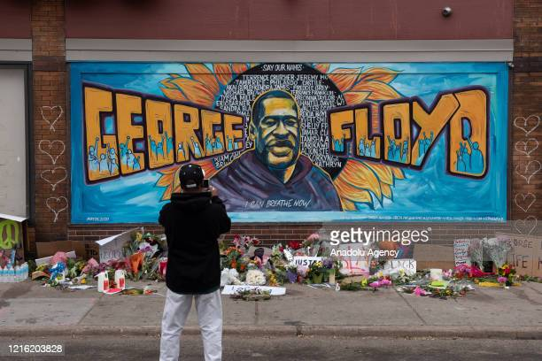 Ronald Scott a central neighborhood resident for more than 10 years takes a photo of the memorial mural over flowers and banners laid in the memory...