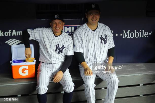 Ronald Torreyes and Masahiro Tanaka of the New York Yankees sit in the dugout prior to Game 3 of the ALDS against the Boston Red Sox at Yankee...