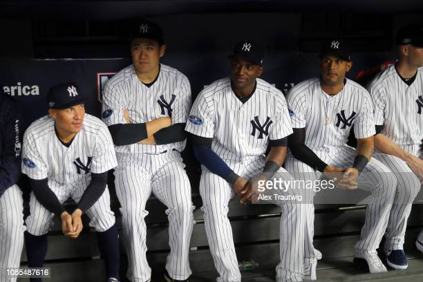 Ronald Torreyes Masahiro Tanaka Adeiny Hechavarria and Aaron Hicks of the New York Yankees sit in the dugout prior to Game 3 of the ALDS against the...
