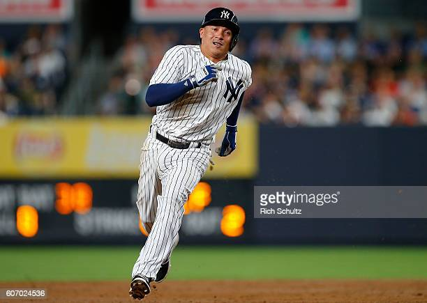 Ronald Torreyes of the New York Yankees advances to third base on a single by Rob Refsnyder against the Los Angeles Dodgers during the third inning...