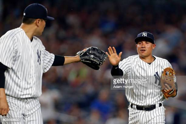 Ronald Torreyes of the New York Yankees high fives Masahiro Tanaka of the New York Yankees against the Texas Rangers during the third inning at...