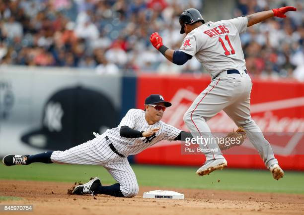 Ronald Torreyes of the New York Yankees makes a diving tag on Rafael Devers of the Boston Red Sox who was out trying to steal second base in the...