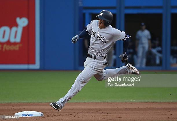 Ronald Torreyes of the New York Yankees races around second base and heads for third base as he hits a triple in the eighth inning during MLB game...