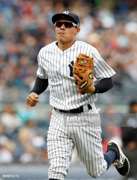 Ronald Torreyes of the New York Yankees runs in to the dugout after throwing out a runner in an MLB baseball game against the Boston Red Sox on...