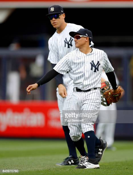 Ronald Torreyes of the New York Yankees throws the ball in from the outfield as Aaron Judge of the New York Yankees towers over him watching in an...
