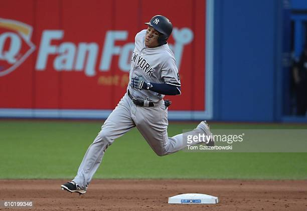 Ronald Torreyes of the Toronto Blue Jays races around second base and heads for third base as he hits a triple in the eighth inning during MLB game...