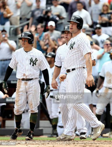 Ronald TorreyesGary Sanchez and Matt Holliday of the New York Yankees wait at home plate for teammate Aaron Judge after Judge drove them all home...