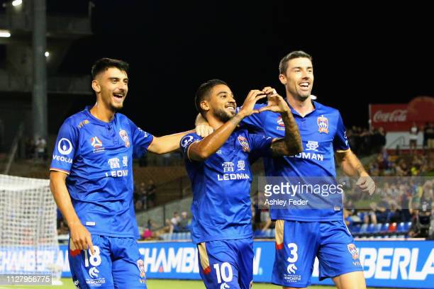 Ronald Vargas of the Newcastle Jets celebrates his goal with John Koutroumbis and Jason Hoffman during the round 18 ALeague match between the...