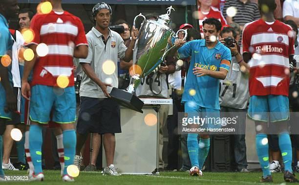 Ronaldinho and Alosnoa Xavi of Barcelona presenting the Franz Beckenbauer Cup after winning the match between Bayern Munich and Barcelona at the...