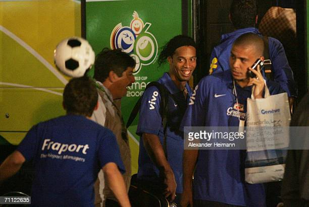 Ronaldinho and Ronaldo of Brazil watch a young boy as he performs some soccer tricks while they and other members of the Brazilian national football...