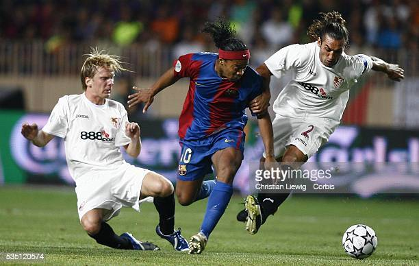 Ronaldinho between Sevilla player Christian Poulsen and Javi Navarro during the 2006 UEFA Super Cup match between FC Barcelona and Sevilla FC
