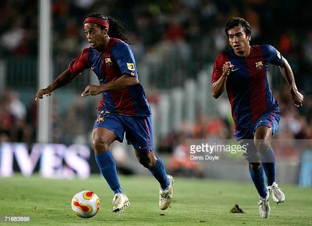 Ronaldinho of Barcelona dribbles the ball beside Giovanni van Bronckhorst during a Supercup 2nd leg match against Espanyol at the Camp Nou stadium on...