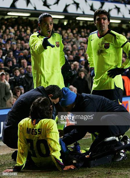 Ronaldinho of Barcelona protest as team mate Lionel Messi receives treatment during the UEFA Champions League Round of 16 First Leg match between...