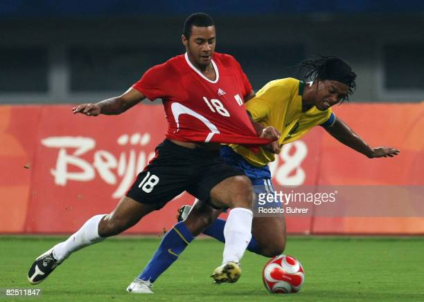 Ronaldinho of Brazil and Moussa Dembele of Belgium compete for the ball during the Bronze Medal Match between Belgium and Brazil at Shanghai Stadium...