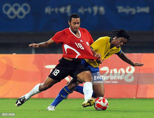 Ronaldinho of Brazil and Moussa Dembele of Belgium fight for the ball during the 2008 Beijing Olympic Games men's football bronze medal match in...