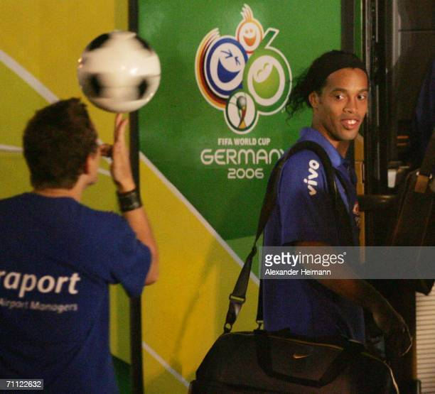 Ronaldinho of Brazil watches a young boy performs football tricks as he arrives with other members of the Brazilian national football team on June 4,...