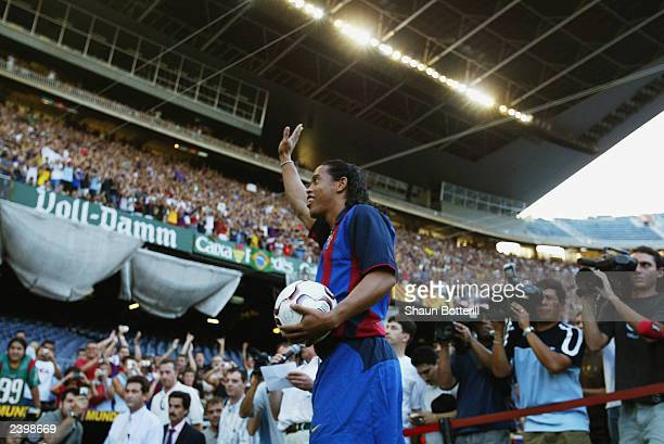 Ronaldinho of Brazil waves to the fans during the Barcelona FC Press Conference for the signing of new player Ronaldinho on July 21 2003 at the Nou...