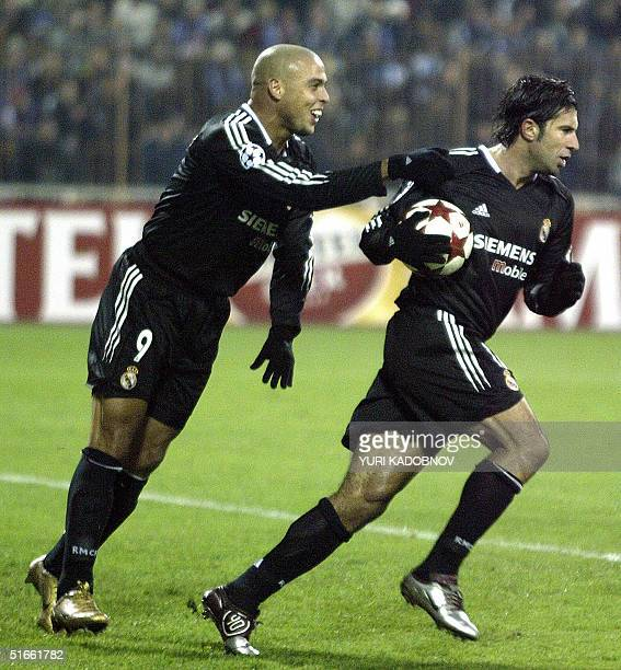Ronaldo congratulates his teammate Figo of Spanish Real Madrid during their UEFA Champions League Group B football match with Dynamo in Kiev 03...
