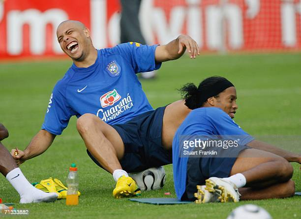 Ronaldo falls off his ball laughing as he relaxes with Ronaldinho of Brazil during the Brazil National Football Team training session for the FIFA...