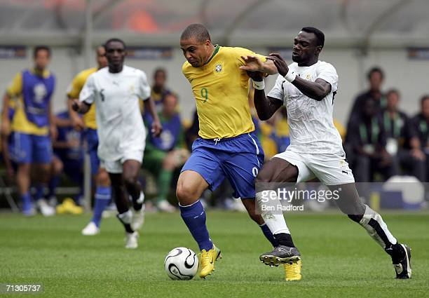 Ronaldo of Brazil holds of the challenge from John Mensah of Ghana during the FIFA World Cup Germany 2006 Round of 16 match between Brazil and Ghana...