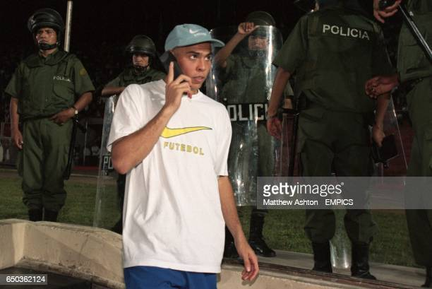 Ronaldo of Brazil speaking on a mobile phone surrounded by Bolivian Police