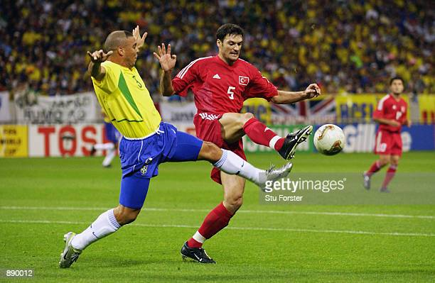 Ronaldo of Brazil tries to tackle Alpay Ozalan of Turkey during the FIFA World Cup Finals 2002 SemiFinal match played at the Saitama Stadium in...