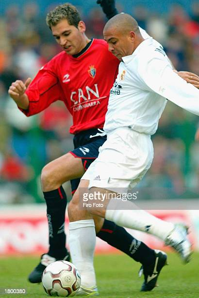 Ronaldo of Real Madrid is challenged by Josetxo of Osasuna during the La Liga match between Osasuna and Real Madrid played at the El Sadar Stadium on...