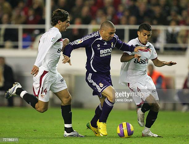 Ronaldo of Real Madrid is tackled by Julien Escude and Dani Alves of Sevilla during the Primera Liga match between Sevilla and Real Madrid at the...