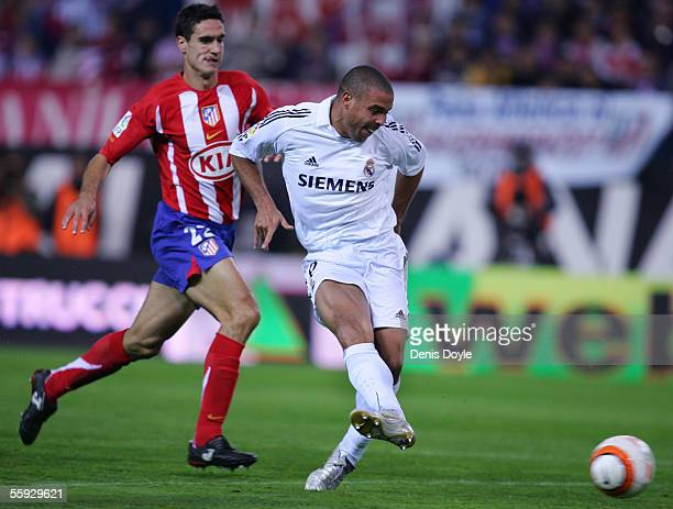 Ronaldo of Real Madrid scores a goal beside Atletico defender Pablo Ibanez during a La Liga match between Atletico Madrid and Real Madrid at the...