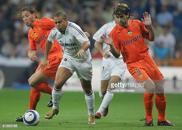 Ronaldo of Real Madrid slips past Helguera of Valencia during the La Liga match between Real Madrid v Valencia at the Bernabau stadium on October 23...