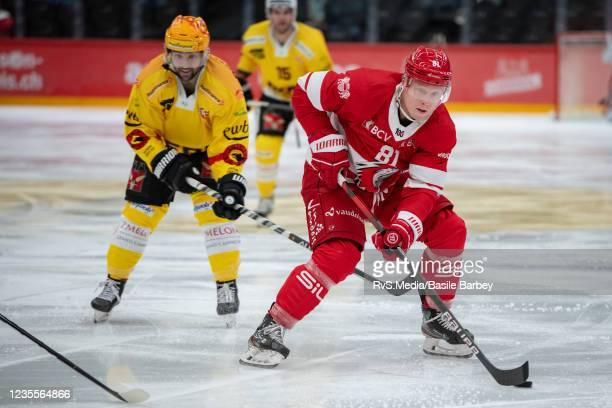 Ronalds Kenins of Lausanne HC carries the puck in front of Cory Conacher of SC Bern during the Swiss National League game between Lausanne HC and SC...