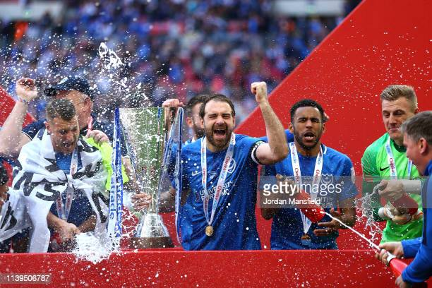 Ronan Curtis of Portsmouth celebrates with team mates as they spray champagne with the trophy following victory the Checkatrade Trophy Final between...
