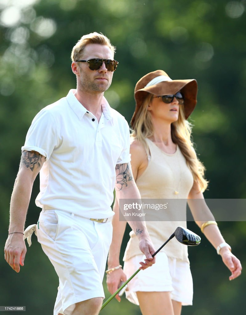 Ronan Keating makes his way down the 18th with girlfriend Storm Keating during the Gary Player Invitational Europe 2013 at Wentworth Golf Club on July 22, 2013 in Virginia Water, England.