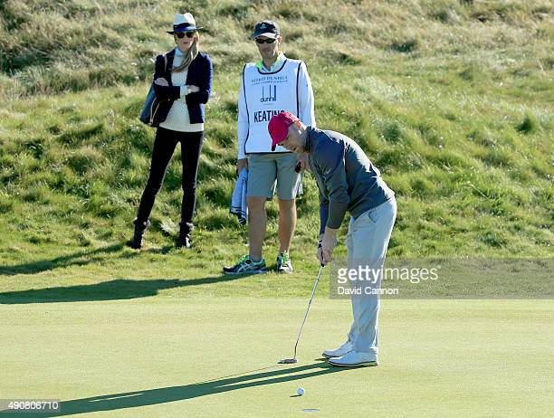 Ronan Keating of Ireland hits a par putt on the second hole watched by his wife Storm Keating and his caddy during the first round of the 2015 Alfred...