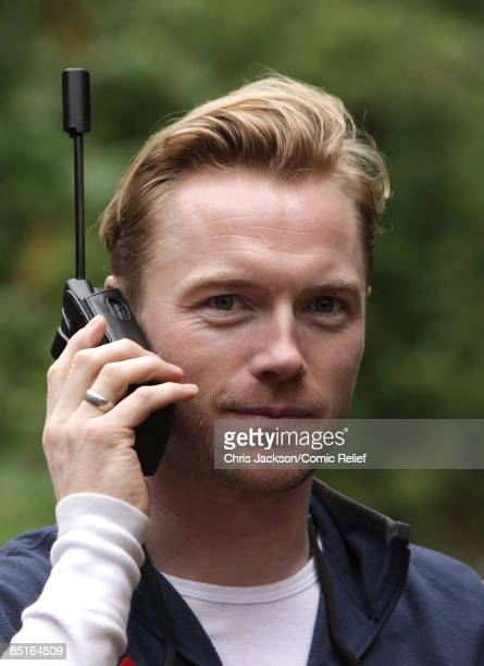 Ronan Keating speaks to his family on sat phone as he takes a rest during trekking on the on the first day of The BT Red Nose Climb of Kilimanjaro on...