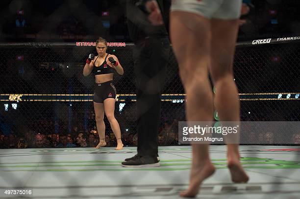 Ronda Rousey stares across the Octagon at Holly Holm in their UFC women's bantamweight championship bout during the UFC 193 event at Etihad Stadium...