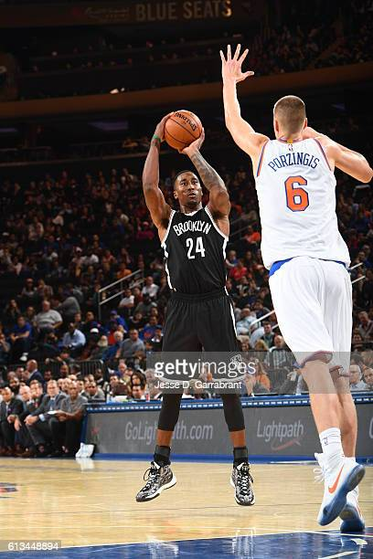 Rondae HollisJefferson of the New York Knicks shoots the ball against Kristaps Porzingis of the Brooklyn Nets in a preseason game at Madison Square...