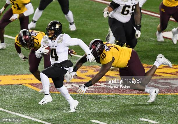 Rondale Moore of the Purdue Boilermakers avoids a tackle by Tyler Nubin and Micah Dew-Treadway of the Minnesota Golden Gophers during the first...
