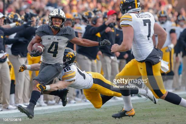 Rondale Moore of the Purdue Boilermakers runs the ball after a catch as John Milani of the Iowa Hawkeyes tries to make the stop at RossAde Stadium on...