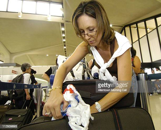 Ronit Rosen of Hod Hasharon Israel moves shampoo nail polish and perfume into her checkin bag after being informed of new security procedures while...