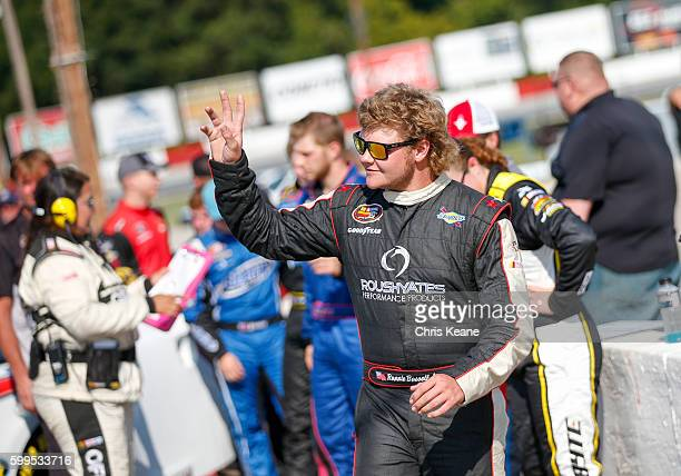 Ronnie Basset Jr driver of the Basset Gutters Ford waves as he is introduced before the NASCAR KN Pro Series East Kevin Whitaker Chevrolet 140 at...