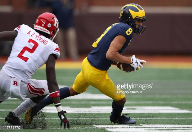 Ronnie Bell of the Michigan Wolverines looks for yards after a third quarter catch behind Avery Young of the Rutgers Scarlet Knights at Michigan...